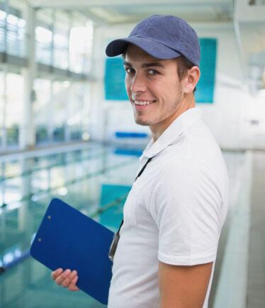 Junger Bademeister/Schwimmlehrer im Schwimmbad
