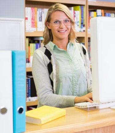 Frau, die in einer Bibliothek arbeitet