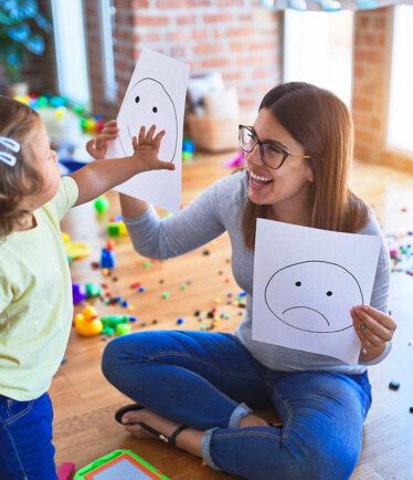 Junge Erziehern, die mit einem Kleinkind spielt
