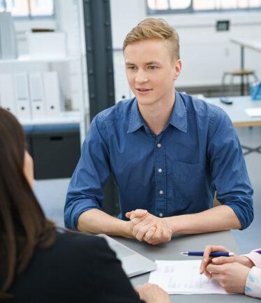 Junger Mann im Gespräch am Arbeitsplatz