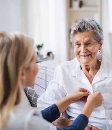 Altenpflegerin, die einer lächelnden älteren Dame hilft